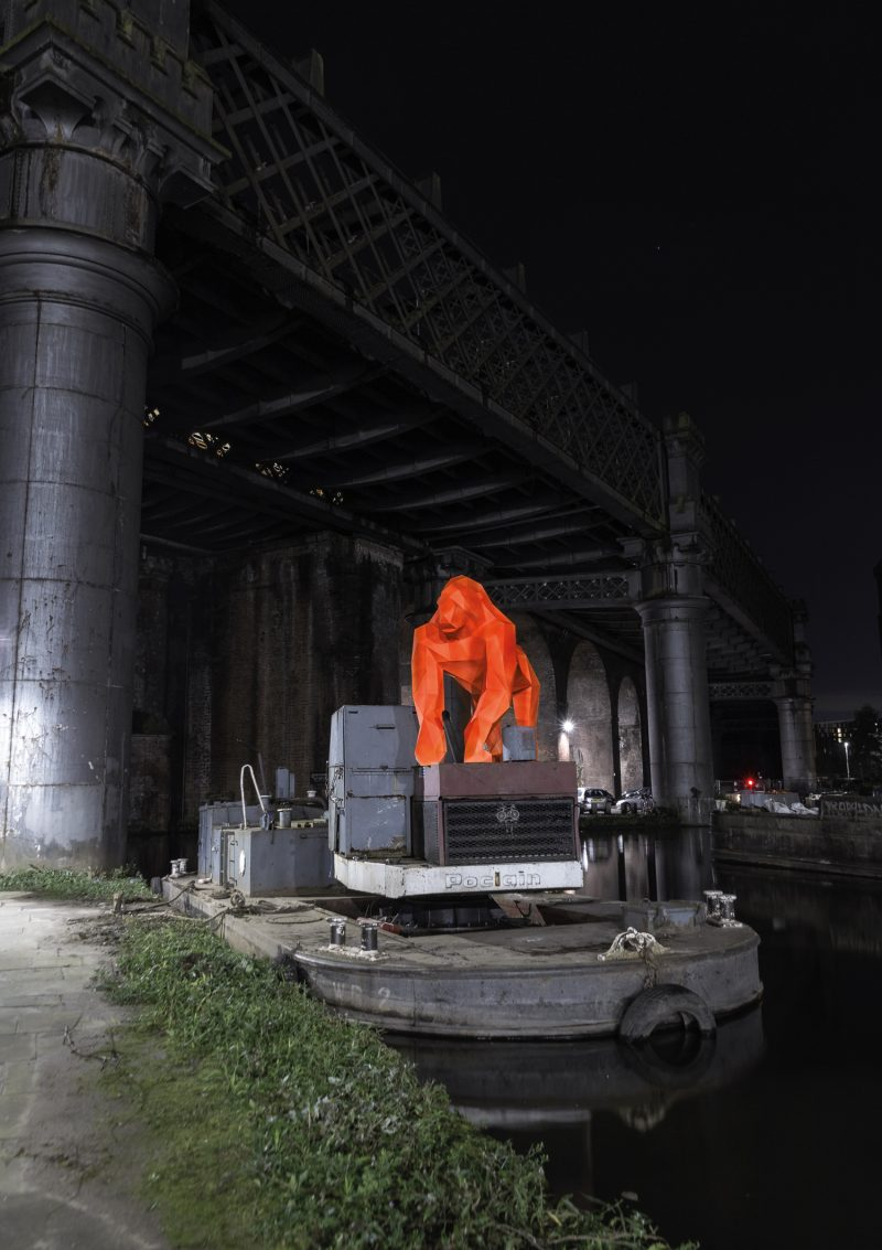 a lifesize 3D model of a bright orange fluorescent gorilla made from cardboard stood on a structure on the canal in Castlefield, Manchester
