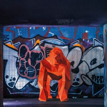 fluorescent orange 3D paper sculpture of a lifesize gorilla in a underground subway in front of a wall of graffiti