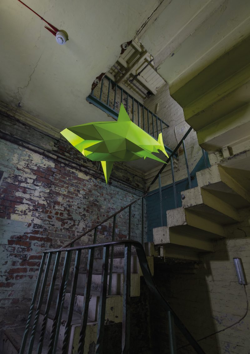 A florescent yellow paper shark sculpture flying mid air with a stone staircase in the background
