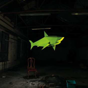 a bright yellow 3D paper shark sculpture that is suspended mid air with a dark background that may be a industrial old building with a chair underneath it