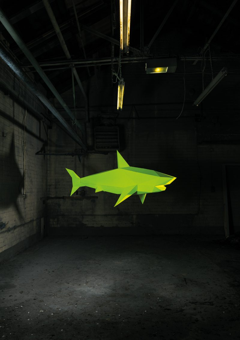 A bright vibrant yellow shark made from paper is suspended mid air in a darkened derelict room