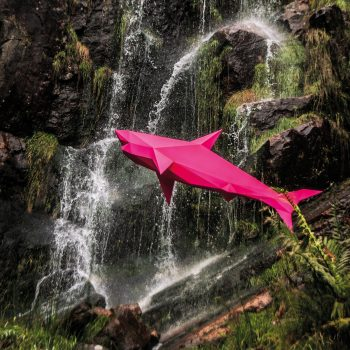 Fluorescent pink 3D shark sculpture made from paper. The vibrant pink shark appears to be flying in front of a beautiful majestic waterfall. Available to purchase as a creative art print by designer Lazerian