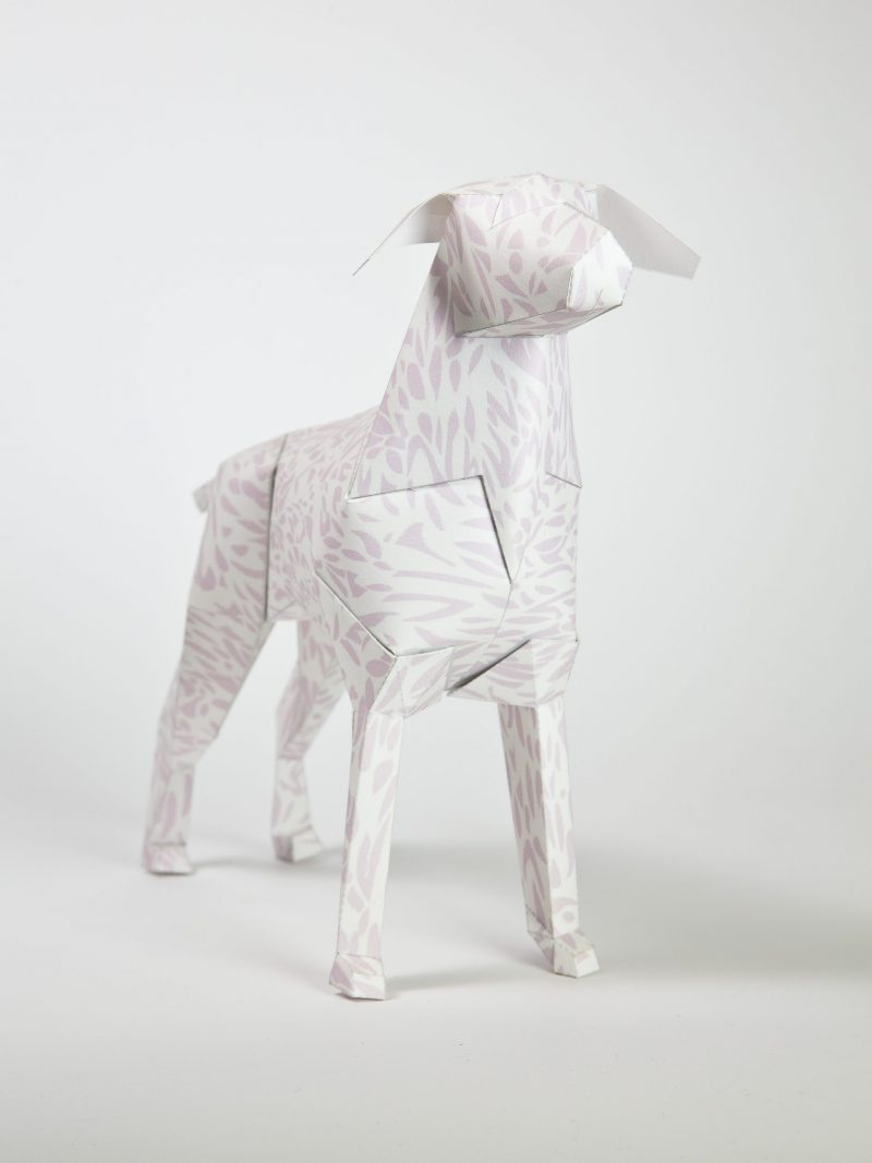 A dog paper model constructed with a very light almost transparent leopard print pattern on it.