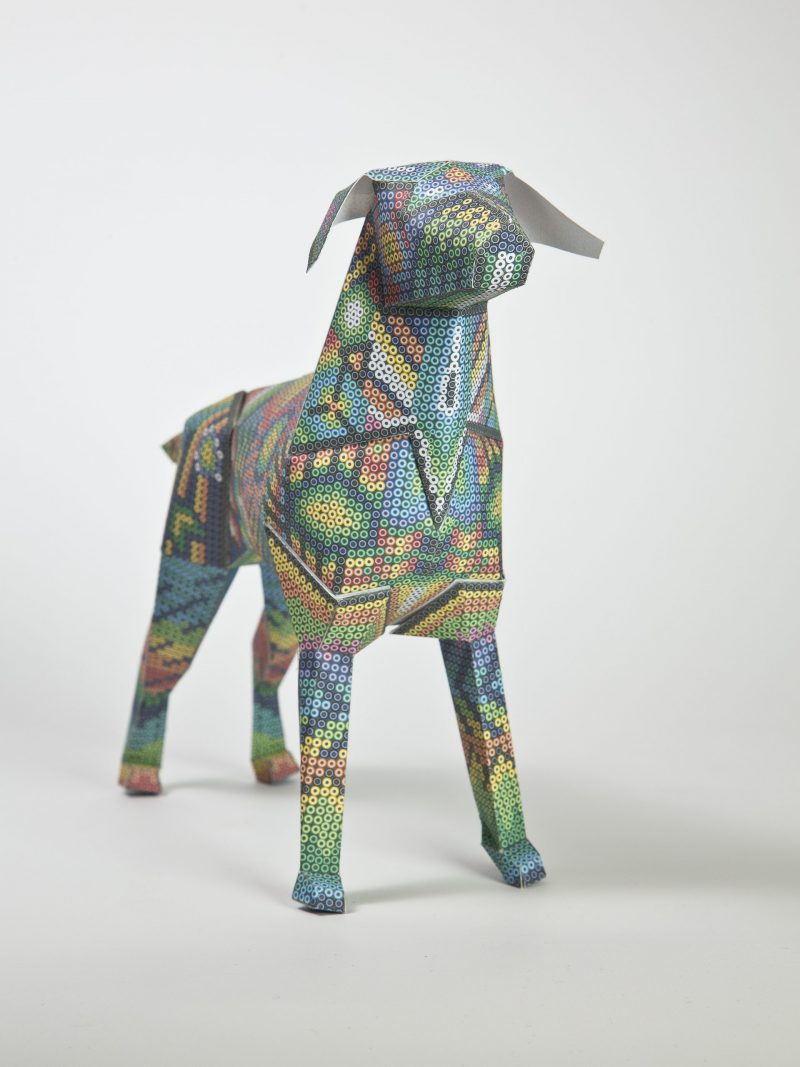 A 3D model of a paper dog with an Aztec stye design created with small circles.