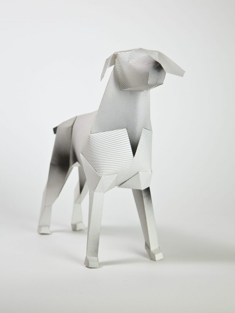 A 3D white paper dog model that has a design of lines on the model, some of the lines meet to make what seems from a distance to appear to look like ink sploshes.