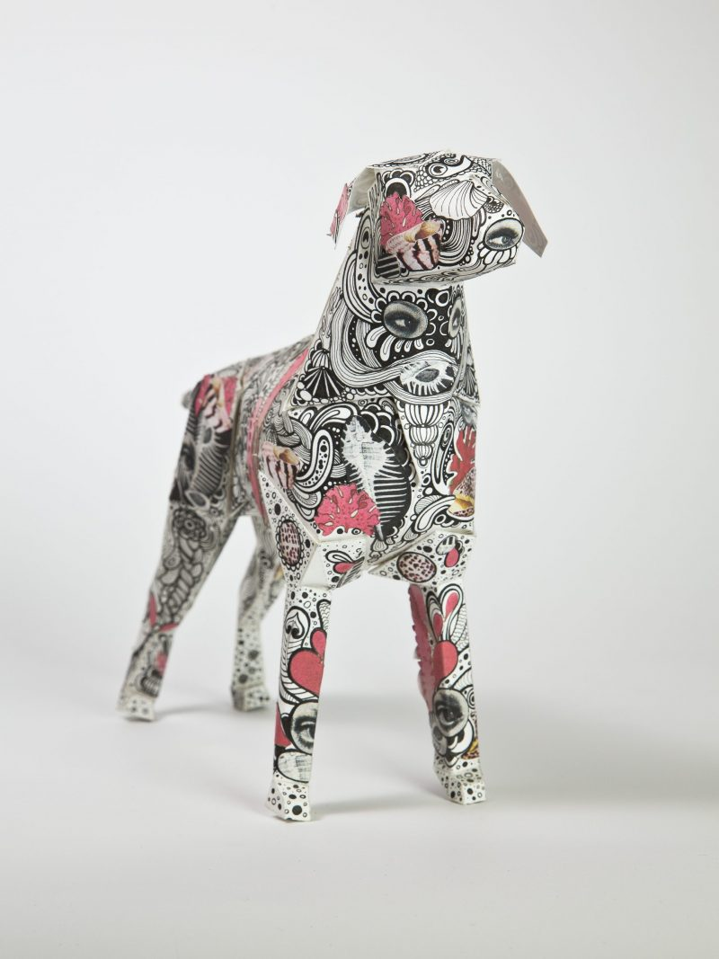A paper dog model with a paisley pattern with pink spotted areas.