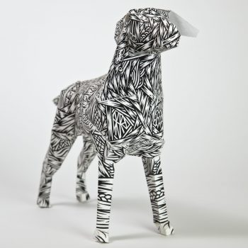 A paper dog model with a black and white pattern