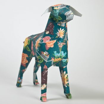 Dog model made from paper with a green background and peach coloured flowers on the design of its coat. Paper dog is a mascot of Lazerian