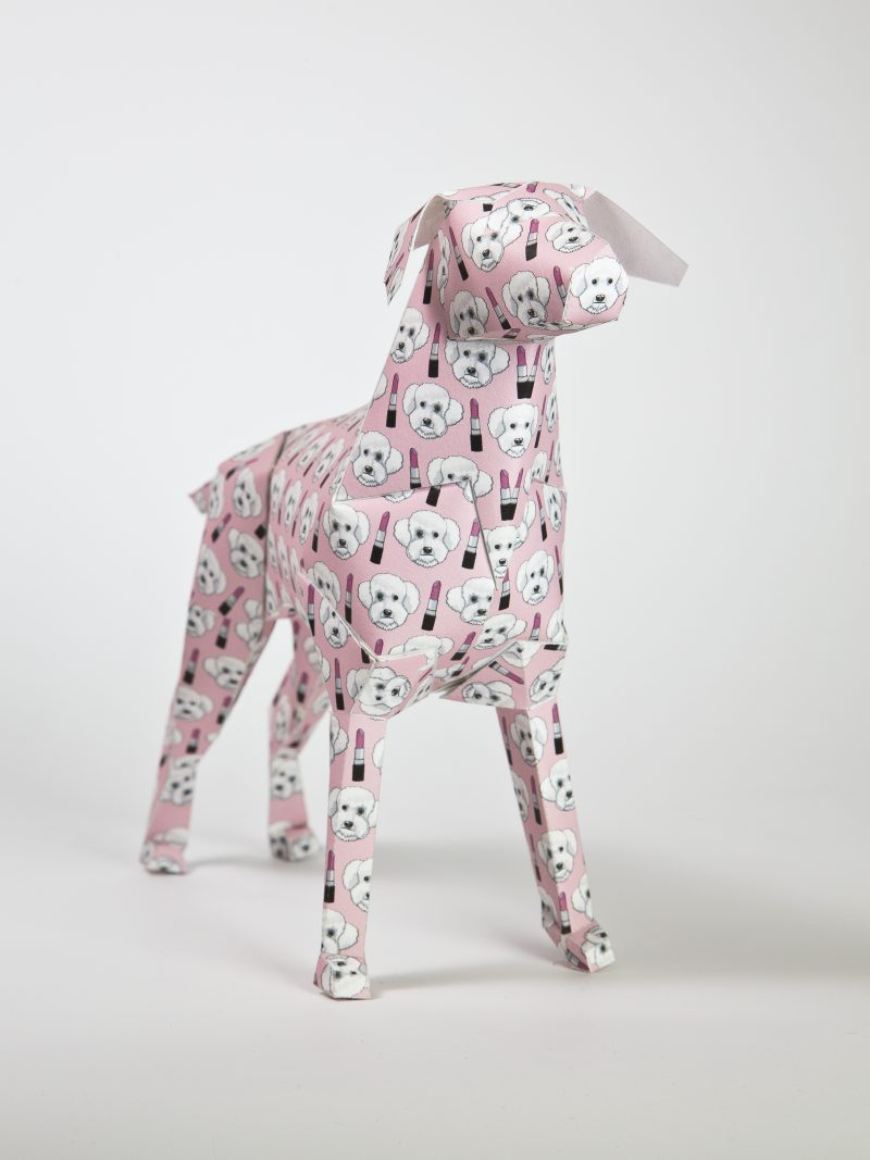 Paper dog model from artist Grande Dame. the 3D paper structure is designed with a baby pink background with images of lipsticks and cute poodle like doggy faces all sporadically around the paper form. Part of an exhibition hosted by designers Lazerian. The paper dog is Lazerian mascot and designers and artist worldwide were invited to customise in their own signature styles