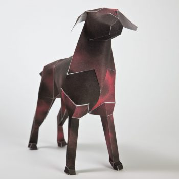 3D paper dog model stood facing the camera on a angle. The dog has a black and red design on it.