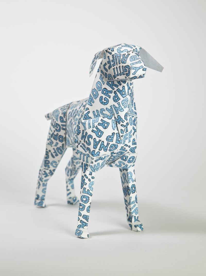 MAin view of a paper dog model with blue bubble writing over it. Spelling out words such as woof, yap, grr and ruff.