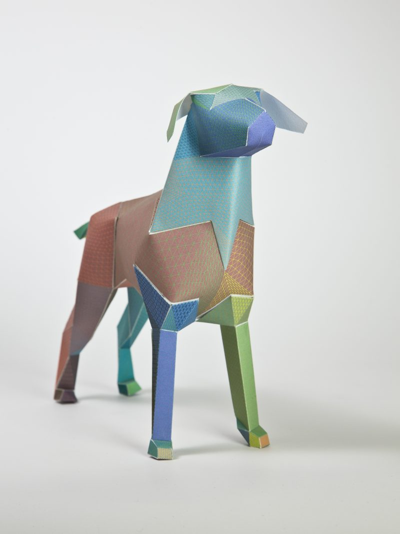 Main view of a paper dog model sculpture. It has a colourful design on it consisting of greens, blues and browns