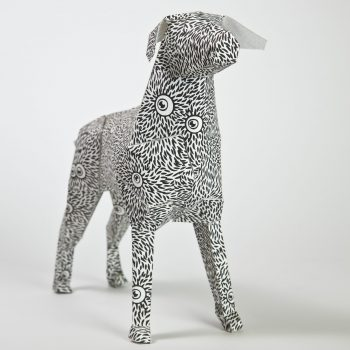 Paper dog model with a black and white pattern and eyes all over the body
