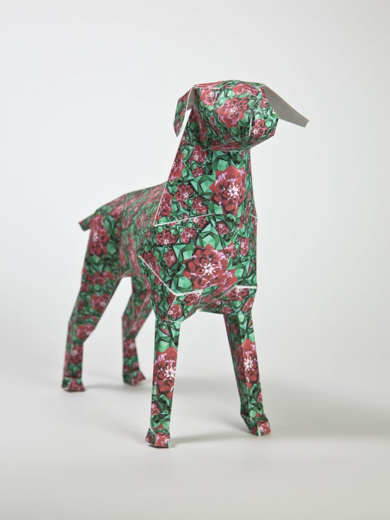Green paper dog 3D model with red flowers on top to make a design feature.
