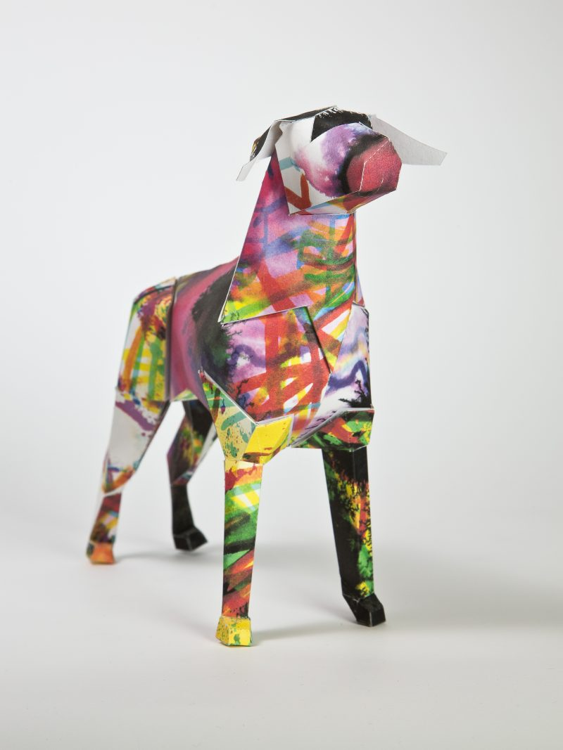 Paper dog model with a illustrated design all over it. Including pink, yellow, green and darker colours are splashed over the paper dog. The design is by Illustrator Kerry Roper. Part of an exhibition by design stuido Lazerian who also have the paper dog as its mascot. Lazerian invited artist and designers to put their own designs onto the paper dog models.