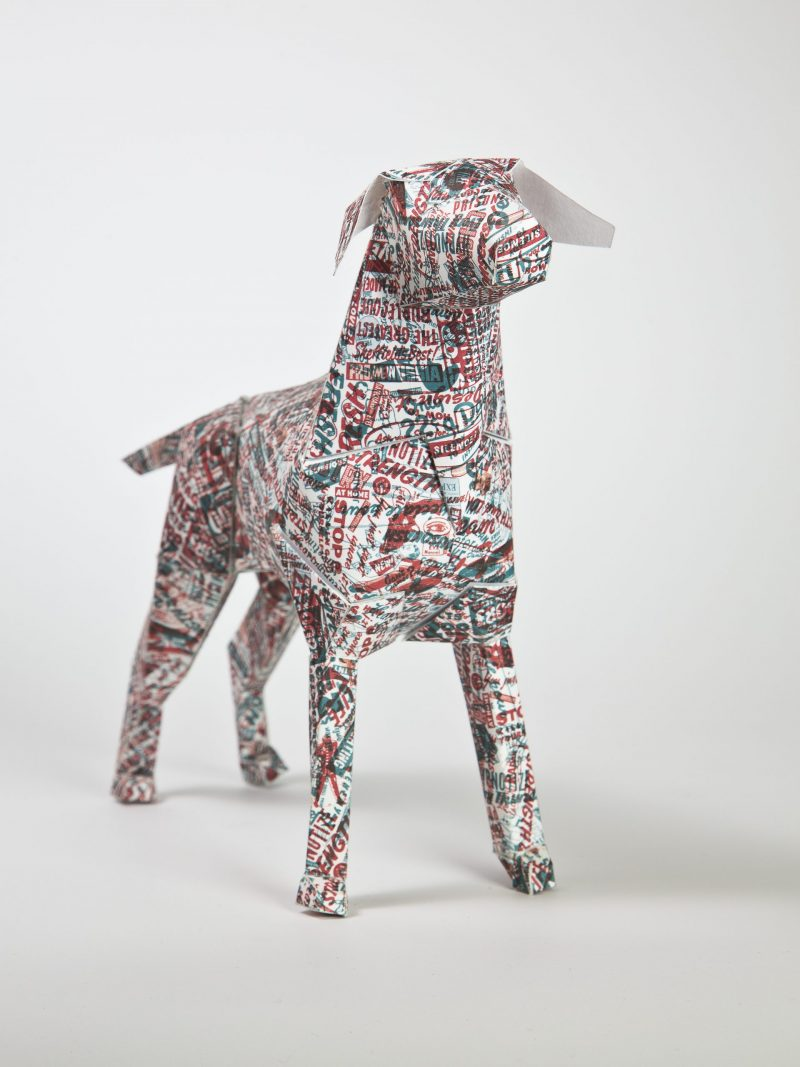 A 3D paper model of a dog with a pattern that resembles a newspaper print with random words printed in red and blue all over its body.