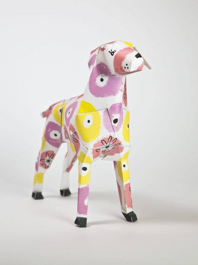 A 3D version os a paper dog sculpture that is decorated with medium sided pink and yellow flower patterns all over it.