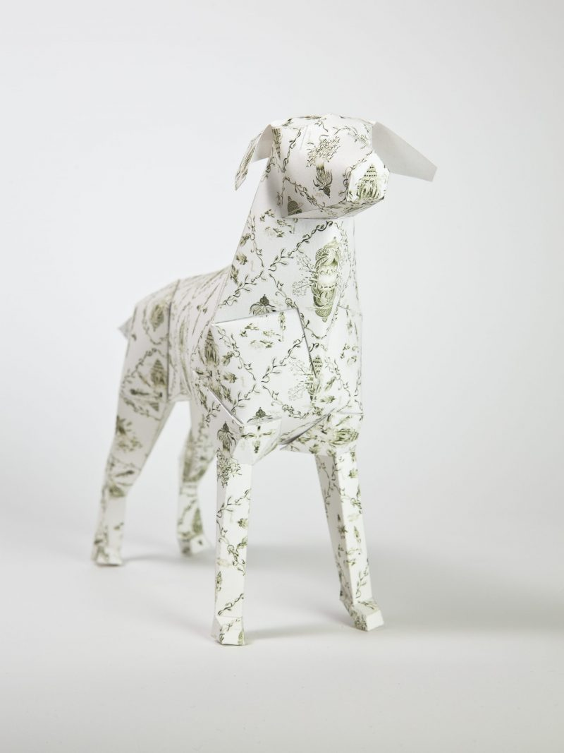 Dog model made from paper with a light coloured traditional style pattern with lines and crosses.