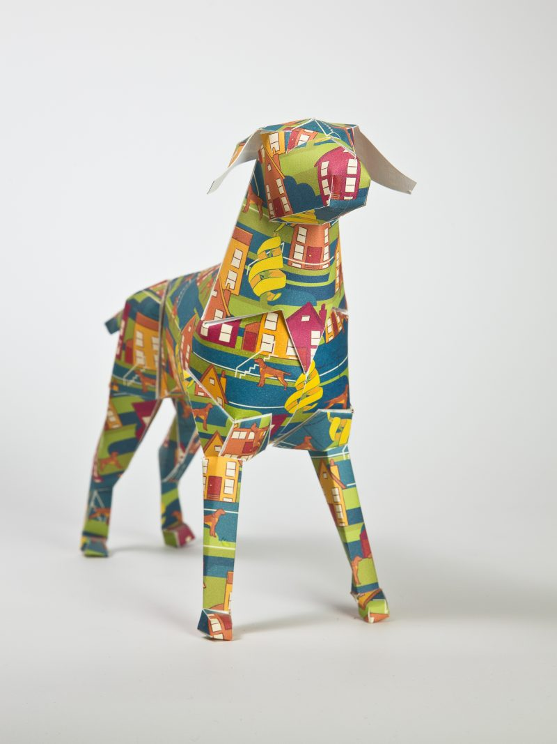 Main view- Paper dog model sculpture. With red, orange and yellow house patterns all over it.