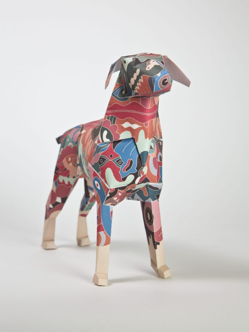Paper dog sculpture with a design on the coat of a pastel camouflage print. Part of an international design exhibition by design leaders Lazerian.