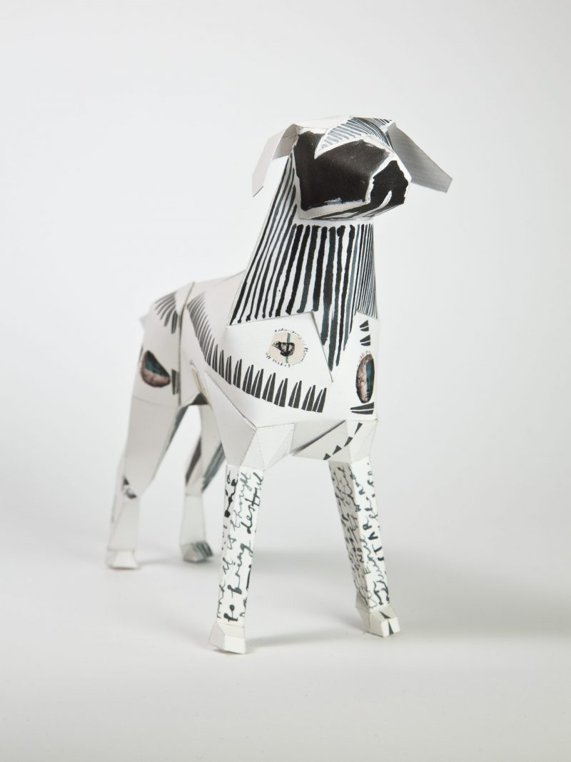Paper dog model of a dog with black pattern on it.