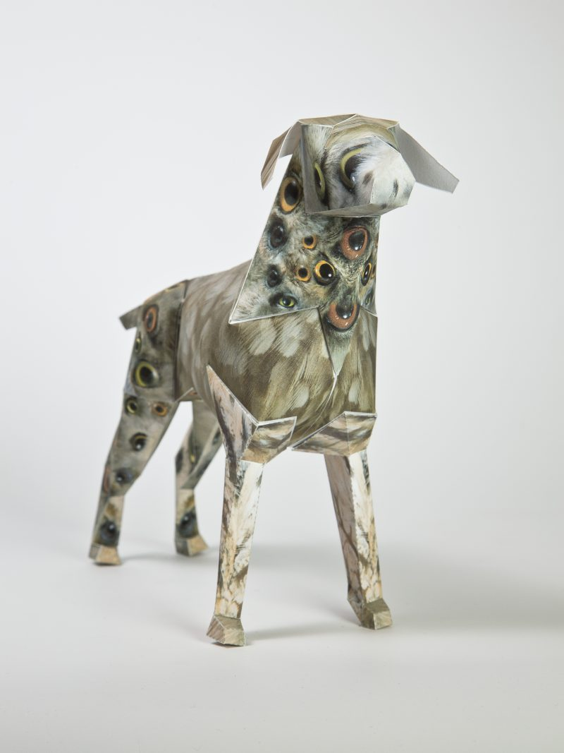 A paper dog model in 3D sculpture form. The design is from artist John Pusateri and features clusters of birds eyes all congregating on the paper dogs face and neck. There is also another cluster on the paper dog models back legs. Part of a internationally renowned design exhibition by design leaders Lazerian. The dog also known as Gerald is the studios mascot and Lazerian decided to invites artists, illustrators, designers and creatives of all kinds to customise the dog sculptures in their own signature designs.