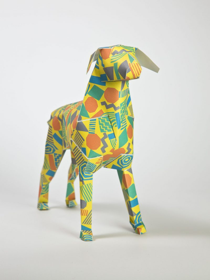 A yellow 3D paper dog sculpture that has a 80's style of orange, blue and purple shapes all over it.