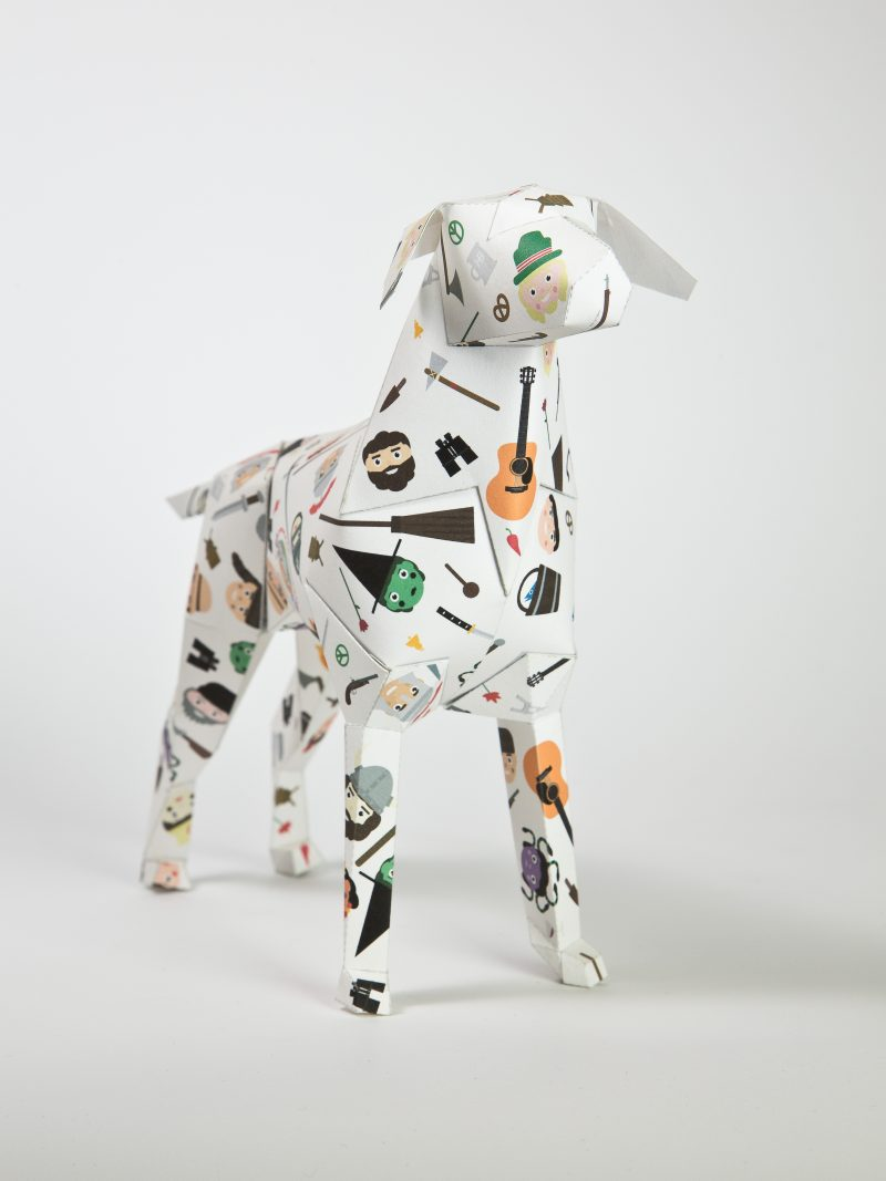 Paper dog model in a 3D sculpture form. Decorated with child like images of faces of storybook characters such as witches, soldiers, cowboys and Indians and Egyptian queens. Designed by childrens illustrator Jamie Malone as part of an exhibition by design studio Lazerian. The dog is a mascot of Lazerian who also set up the project for other designers and artists to showcase their own signature styles onto the paper sculptures.
