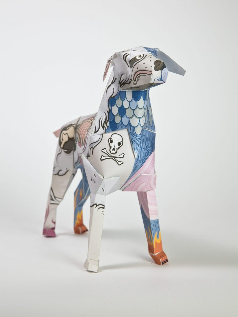 A paper dog model with pirate drawings that look like cartoon style tattoos across its body.