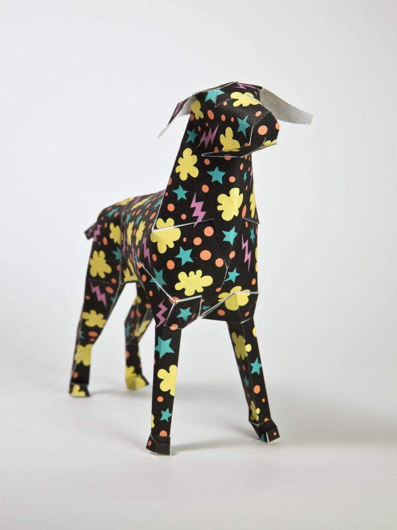 A black paper 3D dog that has yellow cloud shapes, pink lighting bolts and blue stars situated all over the model sculpture.