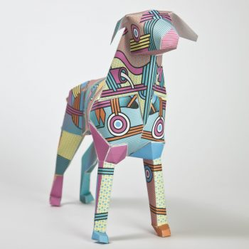 A paper dog model with a vibrant coloured pattern consisting of circles and linear patterns. Colours include yellows, pinks, blues and oranges.