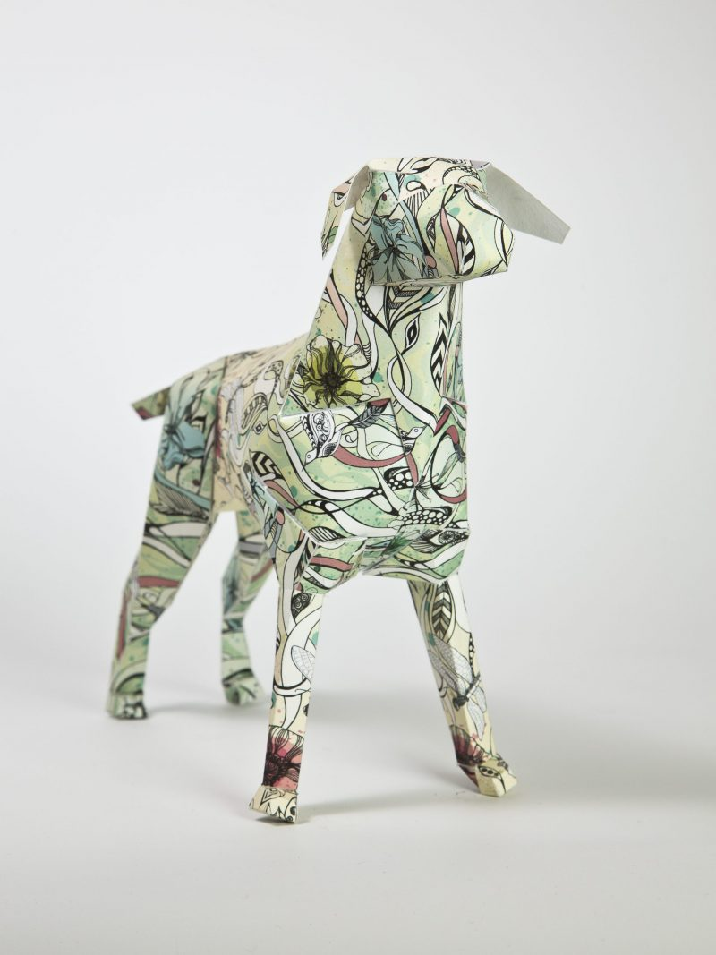 A 3D paper model of a dog with vines, leaves and green flowers on it.