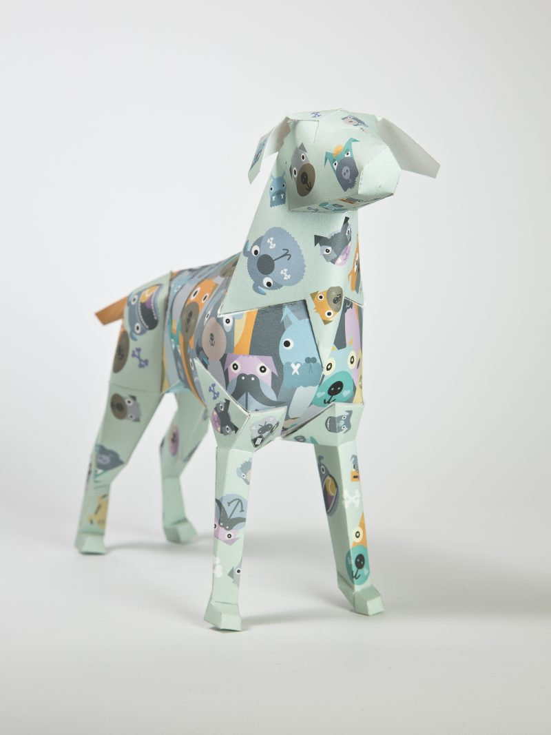 Main view of a paper dog sculpture that has grey and yellow faces of dogs all over it in the style of a child like illustration almost cartoonish. Illustration and design by well respected artist Kev Munday. As part of an exhibition by design studio Lazerian who use the paper dg as their studio mascot.
