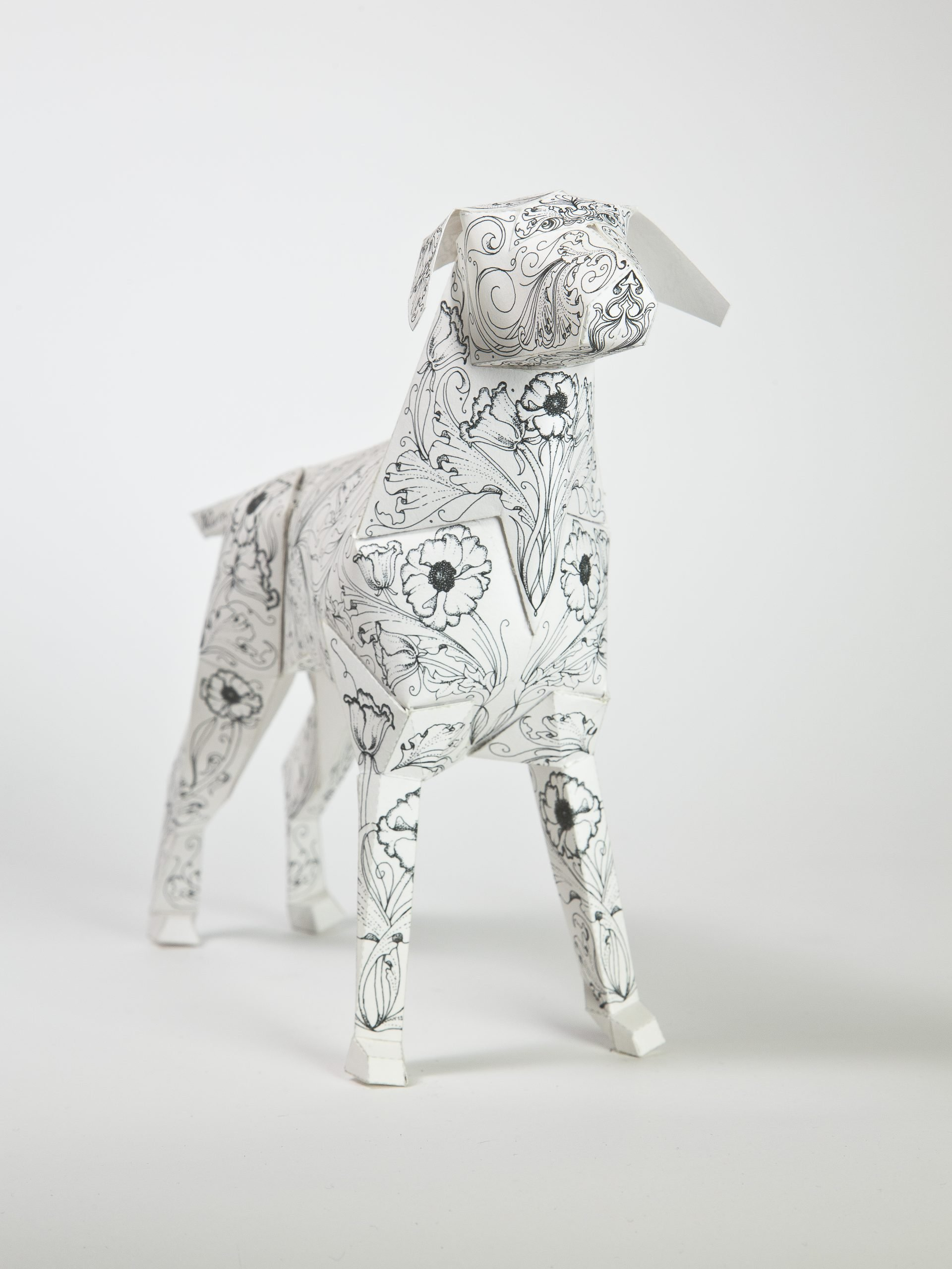 Main view of a dog sculpture made from paper. It has a black and white repeat flower pattern all over it.