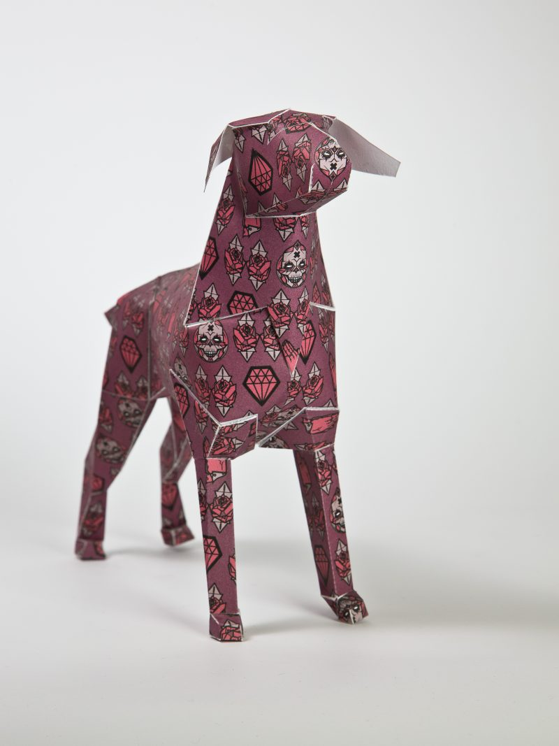 A paper dog sculpture in 3D form with symbols over it that represent mortality, faith and commodity. The artist Gary Milne was one of those chosen by design leaders Lazerian to take part in their exhibition to showcase 101 differently designed dogs by various artist and designer from around the world. Each dog sported a different design to showcase the artist and designers unique and signature styles.