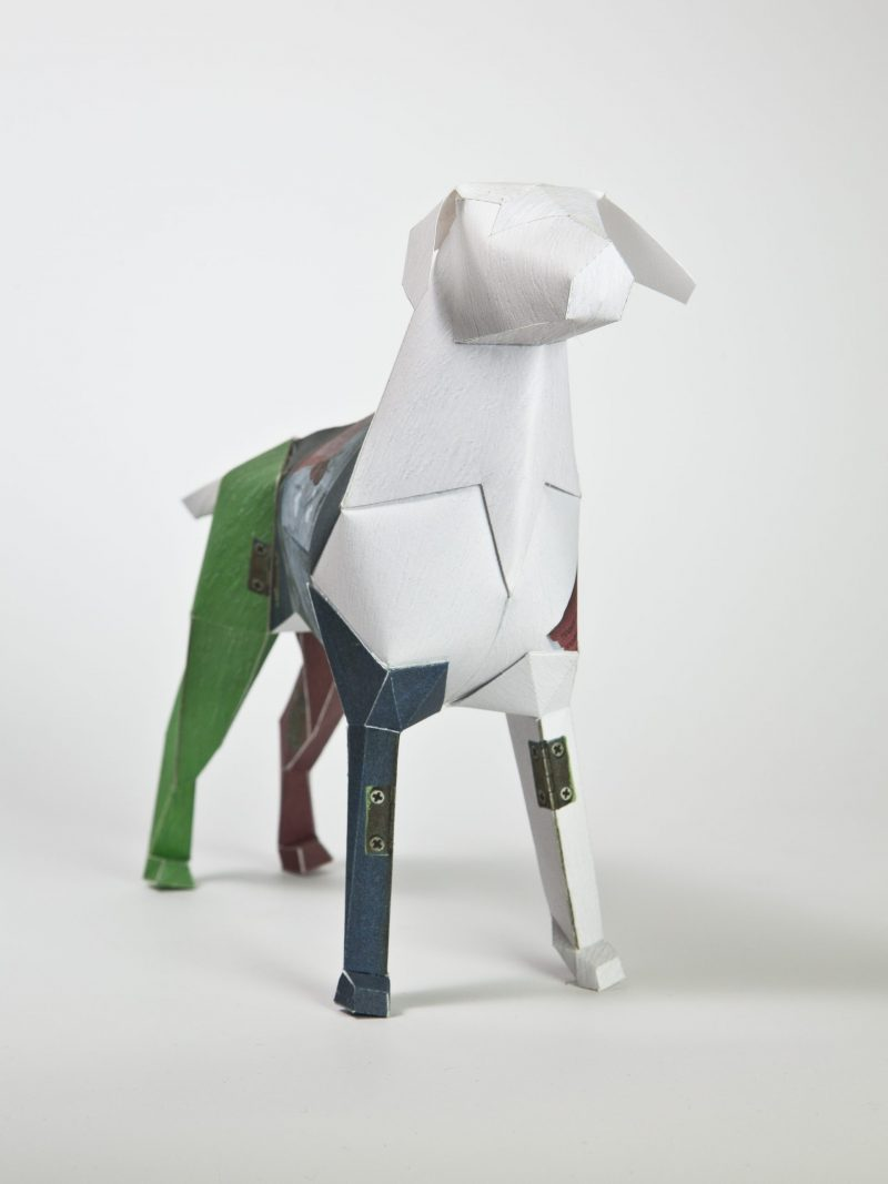 A 3D paper dog sculpture with a white head and neck and a green back leg and a purple front leg.