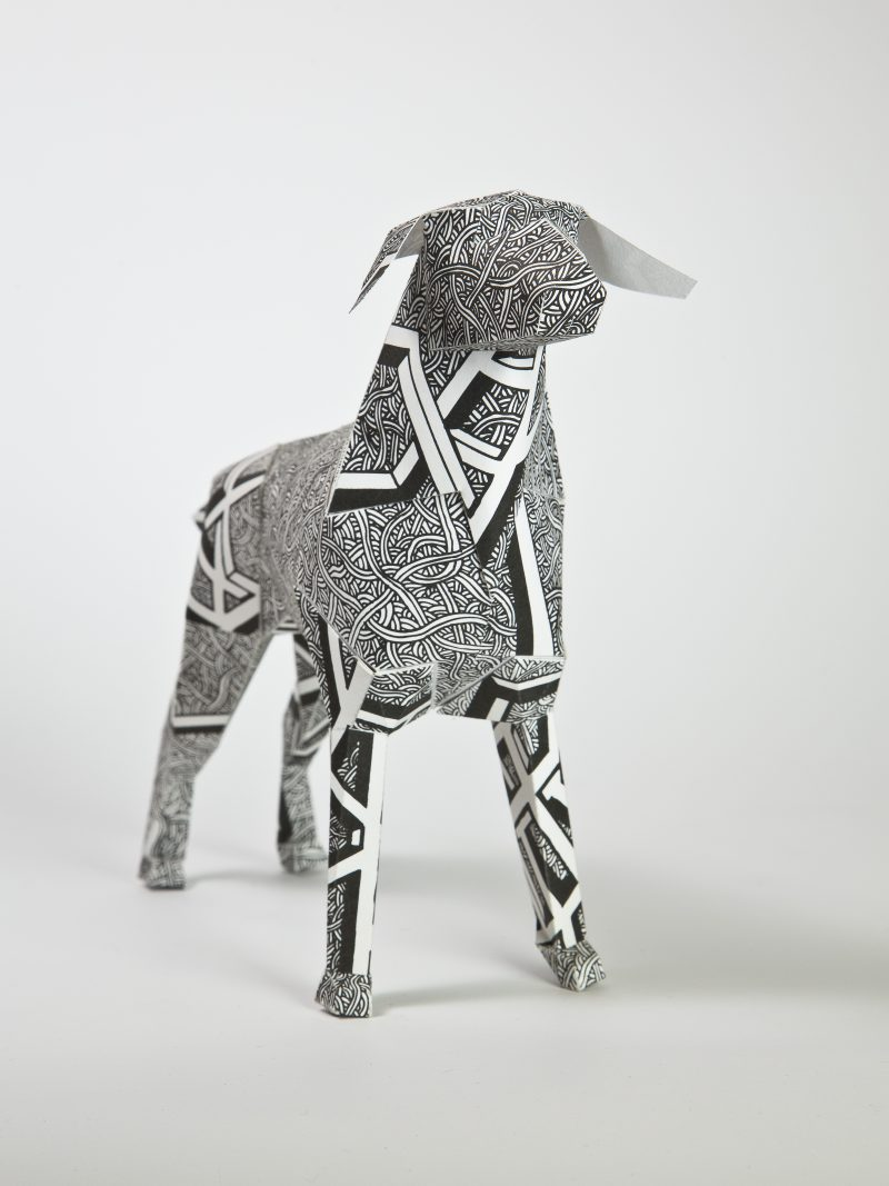 A paper dog sculpture model which is black and white in design. As part of a exhibition by design studio Lazerian. The coat design is by Dave Bain