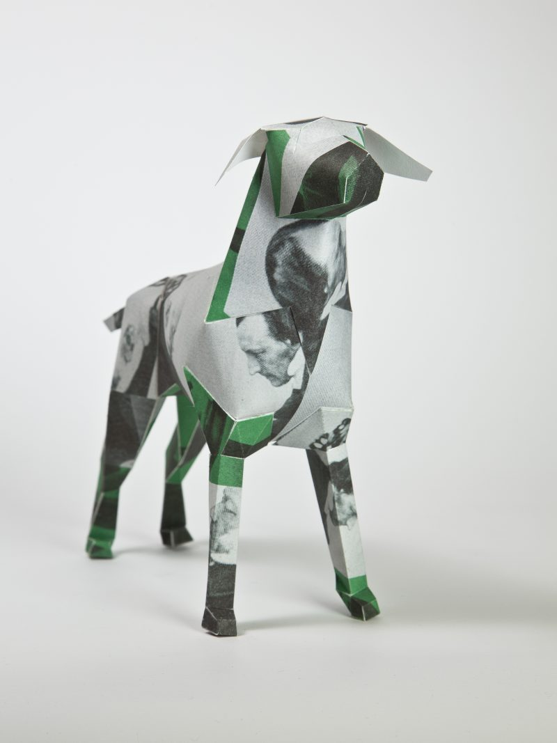 A paper dog model in 3D sculptural form. With green, grey and black and white patches in a collage like style. It also has pieces of photos of a old man in black and white dotted about it. part of a exhibition by leading designers Lazerian of whom the dog is a mascot of. Lazerian invited 101 designers and artists to customise the paper dog sculptures in their own signature styles. The designer of this dog was Hidden Leisure.