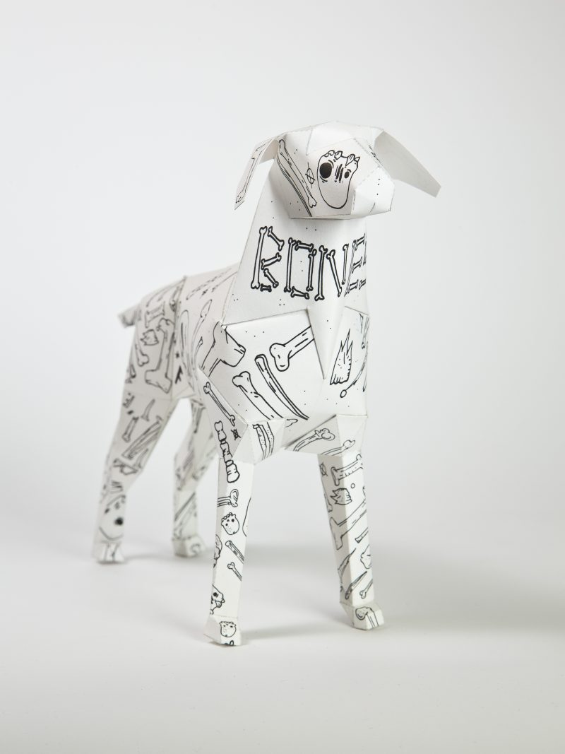 A paper dog sculpture from a exhibition by design leaders Lazerian. the exhibition invited leading artists and designs to showcase their designs on the paper dog models. This design from artist Mr. Millerchip has a white background and black line drawings of skulls and bones.
