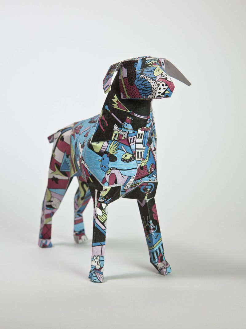 A clourful comic styled patterned paper dog model in a 3D sculpture form.