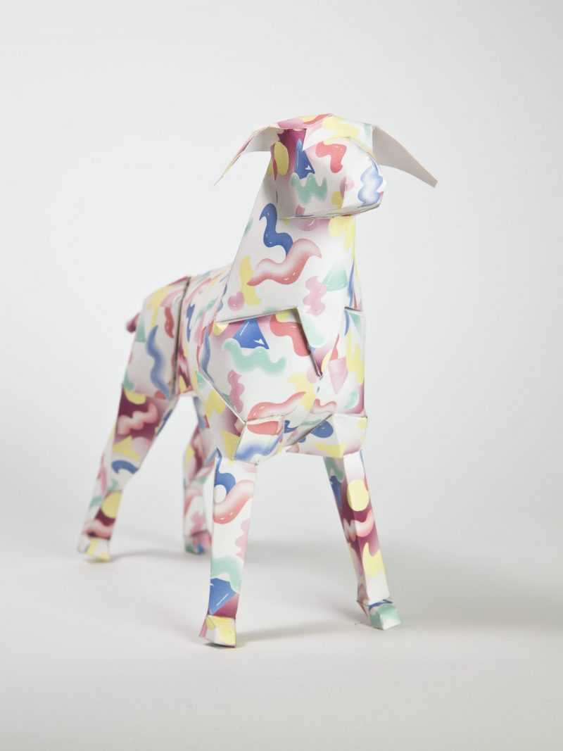 A 3D paper dog model that has red, blue nad yellow squiggles all over it.