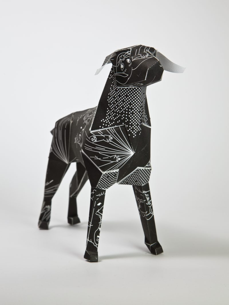 A 3D model of a paper dog sculpture. PArt of an exhibition by design studio lazerian. The dog is black with a white lin drawing all over it consisting of rabbits and ladies faces. The design is by designers DED.