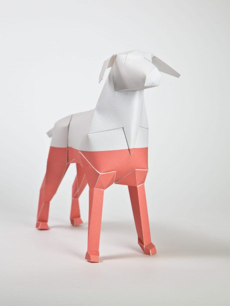 A paper dog 3D sculpture. An artistic designed coat with the top half being white and the bottom half being pink.