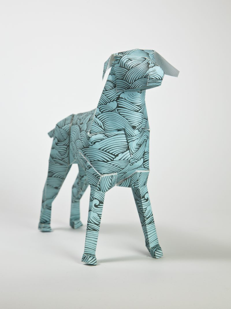 A paper dog model in a 3D sculpture form. Design on the dog is a green/blue colour and a repeat pattern of waves by artist Joe Wilson. PArt of an international exhibition by design leaders LAzerian. The paper dog is the studios mascot and sparked an international exhibition where as leading artist, creatives and designers all customise dthe dog using their own signature styles.
