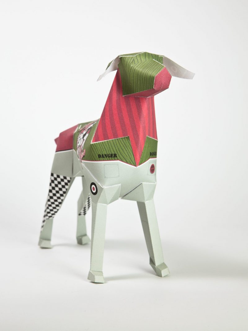 A 3D paper dog model sculpture. It is designed with green, pink and lighter grey colours.