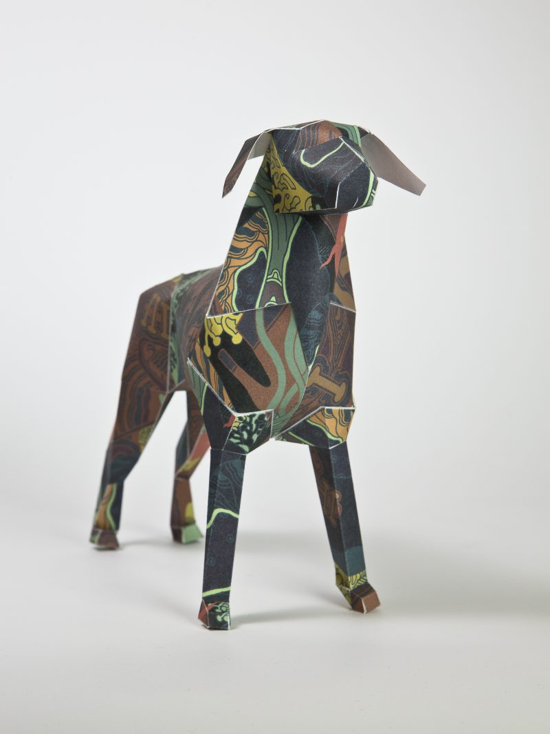 A paper dog model in 3D form. Part of an international exhibition by design studio Lazerian . Inviting designers and artists to customise the dog in their own signature style- this design is by international artist Kristina Collantes. The design has dark colours such as dark green and dark brown that show a pattern that looks like geographical contours.