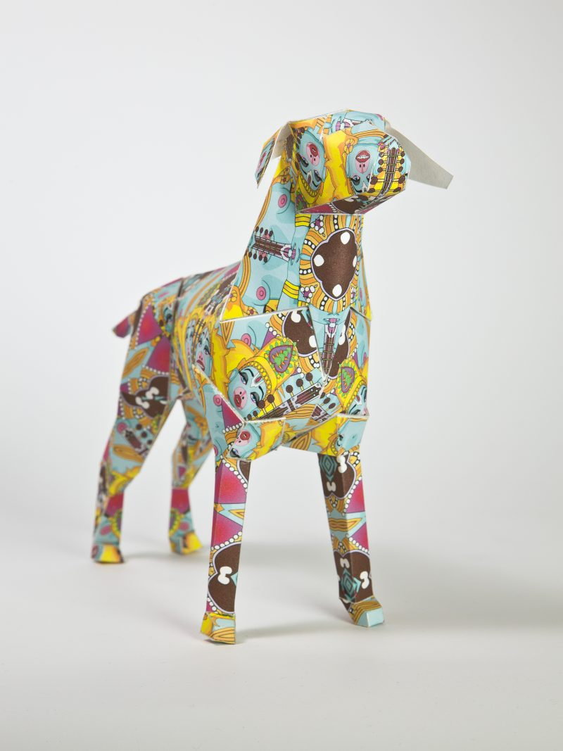 Paper dog sculpture in a 3D form. Part of an international exhibition whereas the dog, who is a mascot for design studio Lazerian, was given to 101 different artists and designers for them to put their own stamp and styled design on it. This design is a Hindu inspired pattern with pinks, yellows and light blues and several faces of female gods sporadically dotted about.