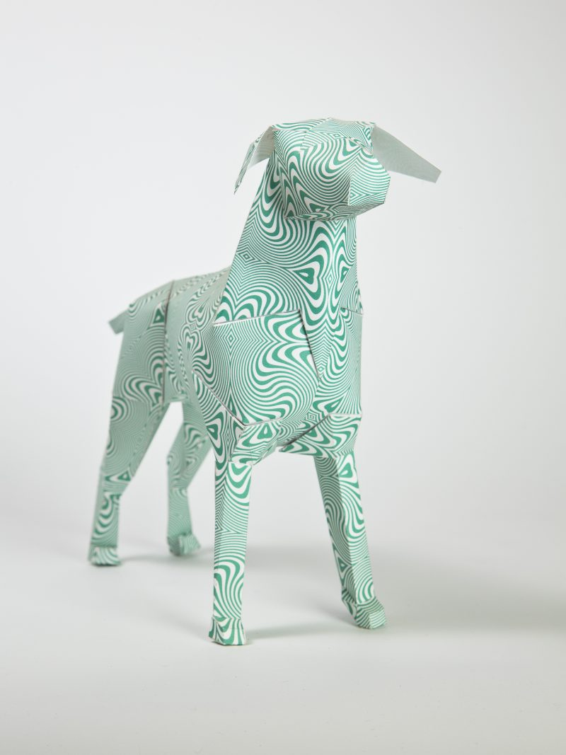 A green lined psychedelic pattern on a 3D paper dog model. the pattern is the type that looks like its moving when you look at it. Part of an international exhibition by design leaders lazerian. 101 designers and artists were all invited to add their signature creative styles as a pattern or design onto the paper dog models. This design is by graphic designers Hawaii.