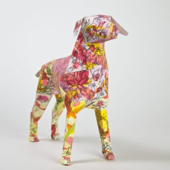 A 3D model of a paper dog with silhouettes of men in black all over the model. It also have sploshes of pinks, yellows, oranges and reds on it