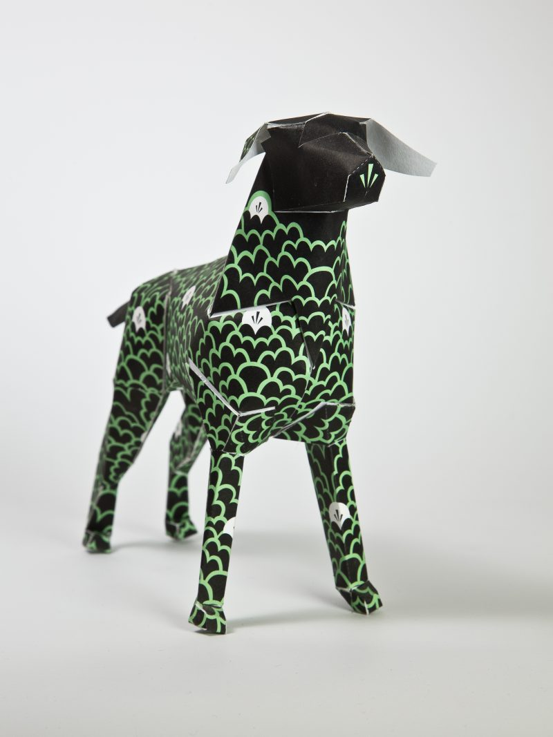 A black model of a paper dog sculpture. Part of an exhibition from design studio lazerian where 101 designers and artist were invited to customise the paper dog sculptures in their own unique contemporary style. This dog has been designed and created using green line formations that resemble the tops of cloud which is what the artist G87 was inspired by.